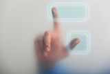 A pointing finger pressing a touch screen button