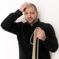 Mann versucht Krawatte zu binden