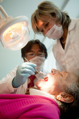 Dentist working on and old patient