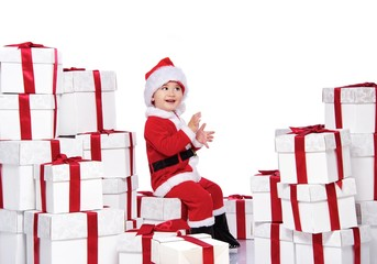Baby boy in Santa Claus costume sitting on gift boxes