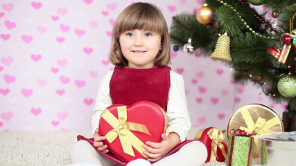 Girl holding a gift sitting on the floor