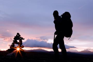 Wanderer und Steinmännchen bei Sonnenaufgang