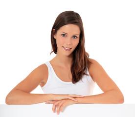 Attraktive junge Frau steht hinter weißer Wand