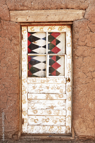 Decorated Door and Adobe Building