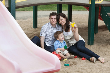 Couple Sitting With Their Son in Playground