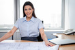 Female Architect Sitting With Blueprints On Desk