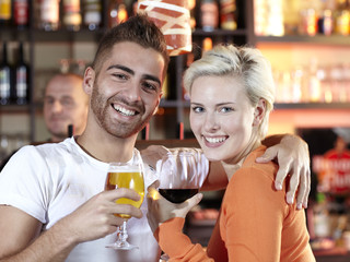 Young couple drinking a glass of wine in a pub