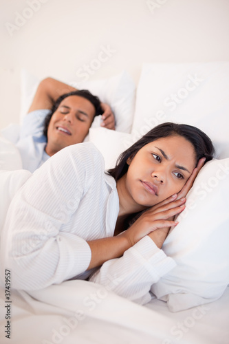 Displeased woman lying next to snoring boyfriend