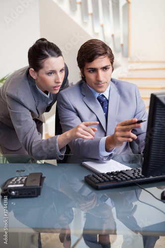 Businessman showing whats on his screen to his colleague