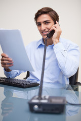 Smiling businessman holding paperwork while on the phone