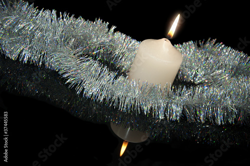 Burning candle with Christmas-tree decoration