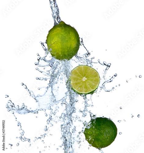 Fresh limes falling in water splash,isolated on white background