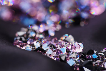 Diamond (small purple jewel) stones heap over black silk cloth b