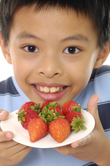 Close up happy little boy holding a strawberries