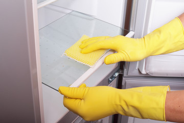 Hands cleaning refrigerator.