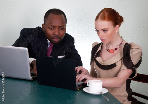 Business colleagues at office desk with two laptops