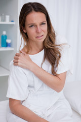 Woman covering painful shoulder