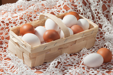 Eggs, yellow and white in a basket on a white lacy napkin