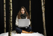 young woman outside in the snow with laptop