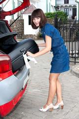 Красивая девушка  грузит чемодан в машину