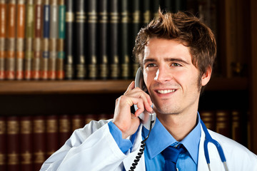 Young doctor talking at the phone in his office