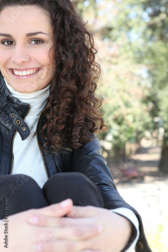 A curly-haired woman relaxing in a park