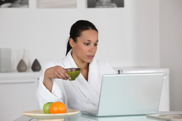 Woman having coffee at home in dressing gown