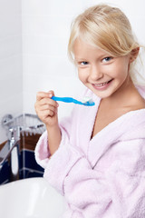 Little girl with a toothbrush in the bathroom