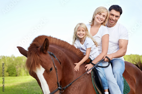 Attractive family on a brown horse