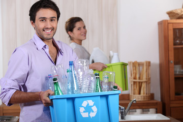 a young couple recycling plastic in their kitchen
