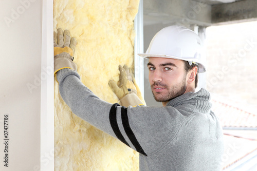Worker installing new insulation