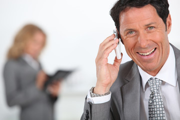 Businessman smiling holding mobile telephone