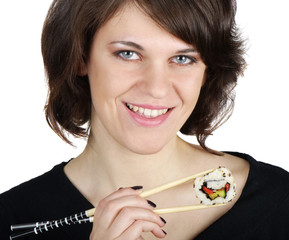 Young smiling woman holding sushi with chopsticks