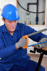 Plumber cutting length of plastic pipe