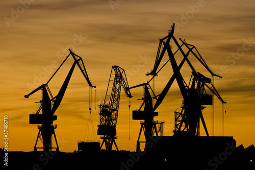 Orange sunset and shipyard cranes