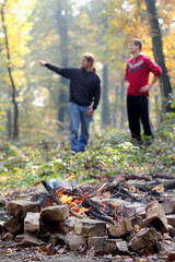 Campfire in forest with young people in background