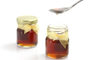 honey dripping from drizzler on top of jar,