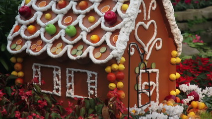 Gingerbread house decorated with fruit and flowers