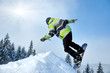 Snowboarder at jump inhigh mountains at sunny day