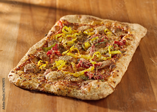 gourmet pizza with sausage and colorful peppers