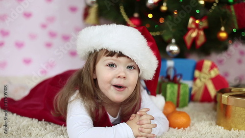 Baby girl in a santa hat lying on the floor. Looking at camera