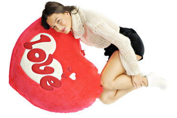 smiling young woman lying on a red heart pillow with love