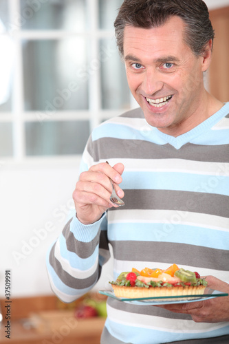 Smiling man eating a fruit flan