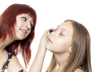 The girl does eyelashes to the little girl