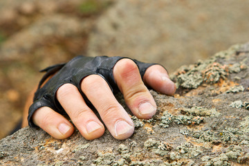 Rockclimber's hand on granite rock in gloves