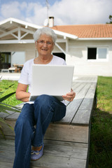 Senior woman using a laptop outside her house