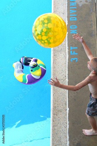 Boy Catching Beach Ball at Pool