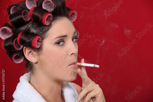 Woman smoking with her hair in rollers