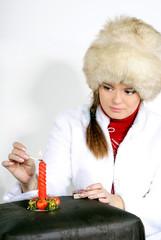 Молодая красивая девушка в меховой шапке зажигает свечу