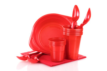 Bright red plastic tableware and napkins isolated on white